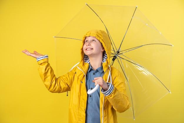 Una bambina sorridente con un cappuccio in testa e un ombrello gioisce mentre piove