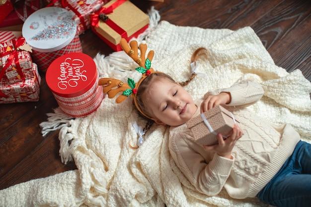 Una bambina sorridente con una fascia di corno di alce è sdraiata sulla schiena, con in mano una confezione regalo