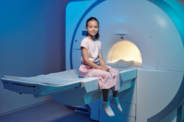 Piccolo paziente sorridente seduto su un lungo tavolo prima o dopo la procedura medica