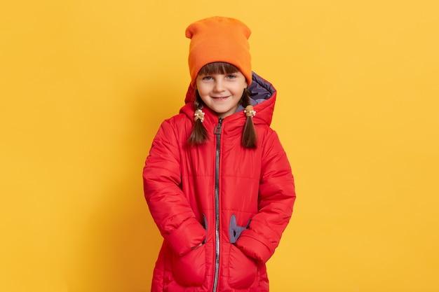 Sorridente poco in giacca rossa isolato sul muro giallo, tenere le mani in tasca
