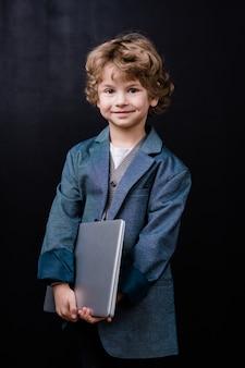 Piccolo scolaro sorridente che tiene portatile piegato mentre levandosi in piedi in isolamento contro lo spazio nero