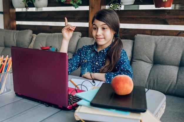 Sorridente scolaretta che fa i compiti davanti a un laptop, è stata in grado di risolvere il compito. insegnamento a distanza.