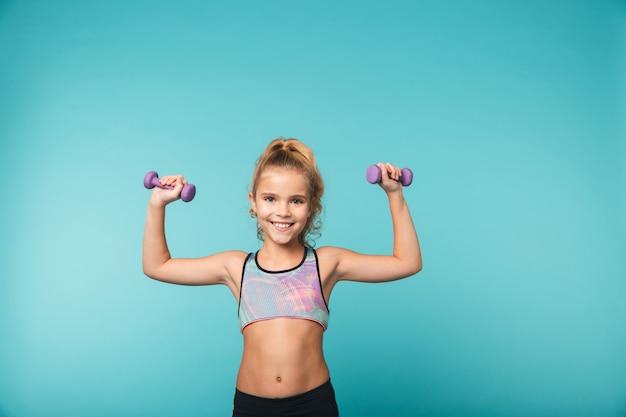 Piccola ragazza sorridente di sport che fa gli esercizi con i dumbbells isolati sopra la parete blu