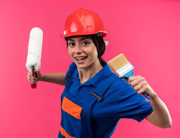 Sorridente guardando la telecamera giovane donna costruttore in uniforme tenendo la spazzola a rullo con pennello