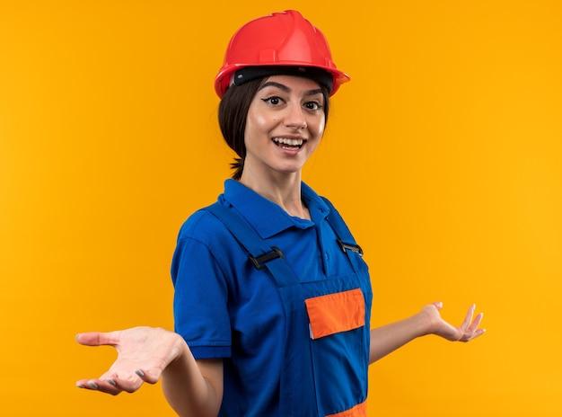 Sorridente guardando la telecamera giovane donna costruttore in uniforme allargando le mani
