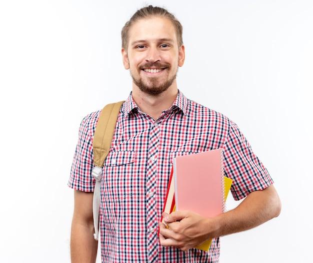 Sorridente guardando fotocamera giovane studente ragazzo che indossa uno zaino in possesso di libri isolati su muro bianco