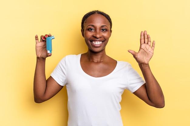 Sorridere e sembrare amichevole, mostrando il numero cinque o il quinto con la mano in avanti, conto alla rovescia. concetto di asma