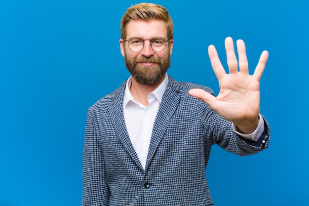 Sorride e sembra amichevole, mostrando il numero cinque o il quinto con la mano in avanti, il conto alla rovescia