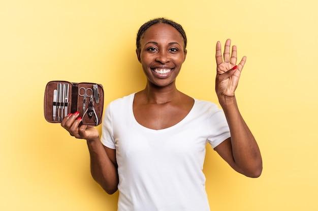 Sorridere e sembrare amichevole, mostrando il numero quattro o il quarto con la mano in avanti, conto alla rovescia. concetto di strumenti per unghie