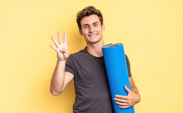 Sorridere e sembrare amichevole, mostrando il numero quattro o il quarto con la mano in avanti, conto alla rovescia. concetto di tappetino da yoga