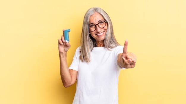 Sorridere e sembrare amichevole, mostrando il numero uno o il primo con la mano in avanti, conto alla rovescia. concetto di asma