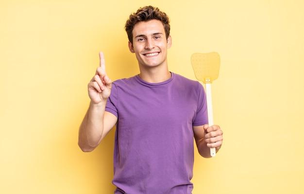 Sorridere e sembrare amichevole, mostrando il numero uno o il primo con la mano in avanti, conto alla rovescia. uccidere mosche concetto