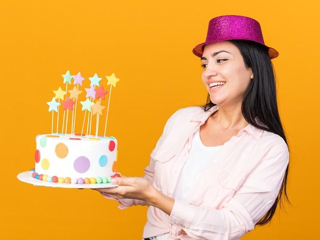 Sorridente guardando lato giovane bella donna che indossa cappello da festa tenendo la torta isolata sulla parete arancione