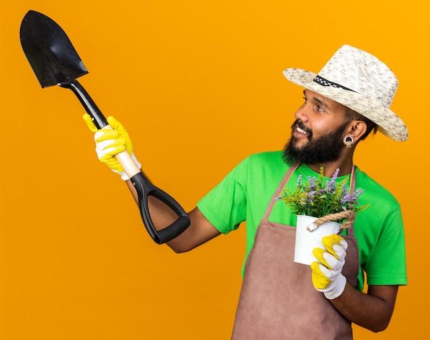 Sorridente guardando lato giovane giardiniere afro-americano ragazzo che indossa cappello da giardinaggio e guanti che tengono vanga con fiore in vaso di fiori