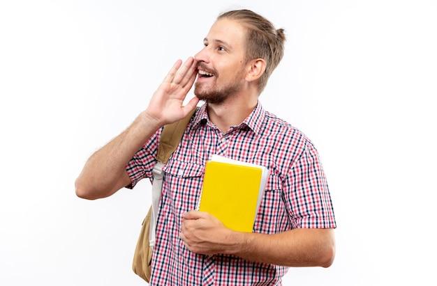 Sorridente guardando lato giovane studente che indossa uno zaino in possesso di libri che chiama qualcuno isolato sul muro bianco