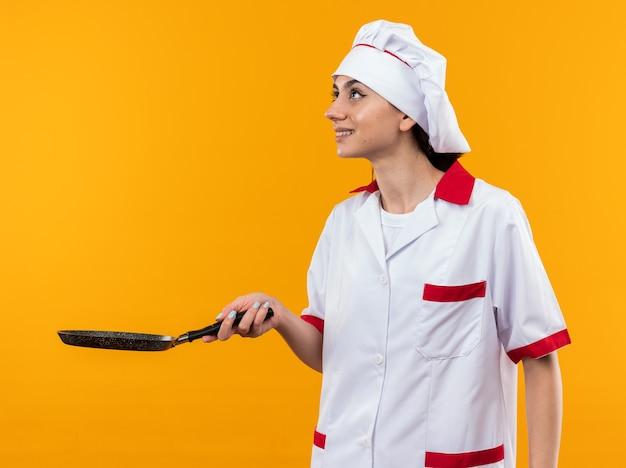 Sorridente guardando la giovane bella donna in uniforme da chef tenendo fuori la padella sul lato isolata sulla parete arancione