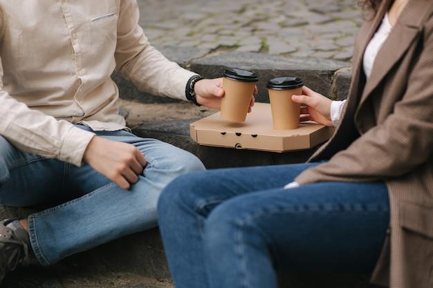Coppie sorridenti di amore che si siedono sulle scale all'aperto e tengono le tazze di caffè