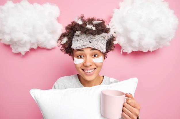 Sorridente bella giovane donna si sveglia dopo aver dormito ha le piume nei capelli beve caffè aromatico tiene il cuscino subisce procedure di bellezza prima di andare al lavoro