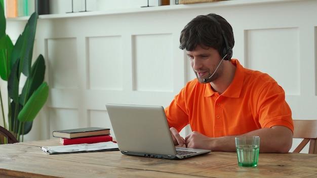 Operatore di call center maschio sorridente che fa il suo lavoro con un auricolare.