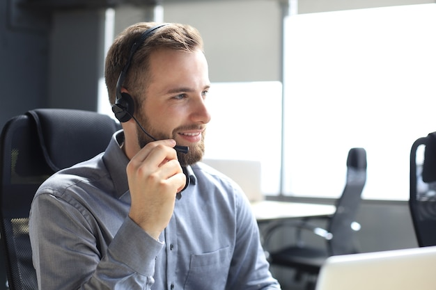 Sorridente operatore di call center maschio con cuffie seduto in un ufficio moderno, consultando informazioni online in un laptop, cercando informazioni in un file per essere di aiuto al cliente