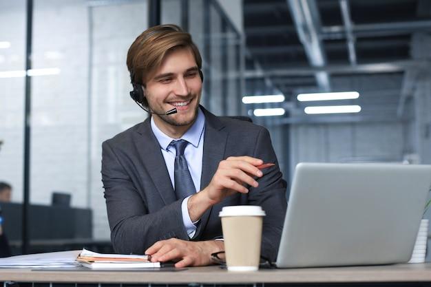 Operatore di call center maschio sorridente con cuffie seduto in un ufficio moderno, consultando informazioni online in un laptop, cercando informazioni in un file per essere di aiuto al cliente.