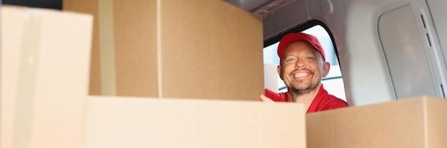 Il corriere maschio sorridente estrae la scatola di cartone dall'auto