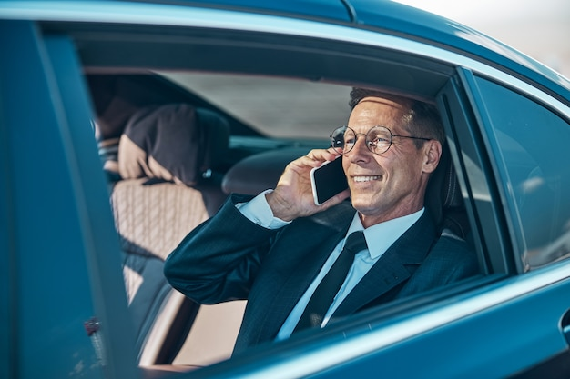 Un uomo sorridente con gli occhiali e un abito elegante è seduto in macchina e parla al cellulare