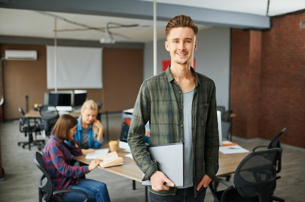 Lo specialista it maschio sorridente tiene il computer portatile in ufficio. programmatore web o designer sul posto di lavoro, occupazione creativa. moderna tecnologia dell'informazione, team aziendale