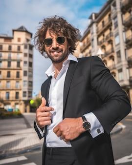 Sorridente modello maschile in posa fuori per strada