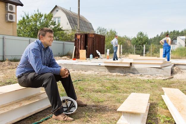 Sorridente ingegnere di cantiere maschio in camicia a maniche lunghe blu a righe seduto su piattaforme bianche vicino all'area del progetto con casco bianco a terra