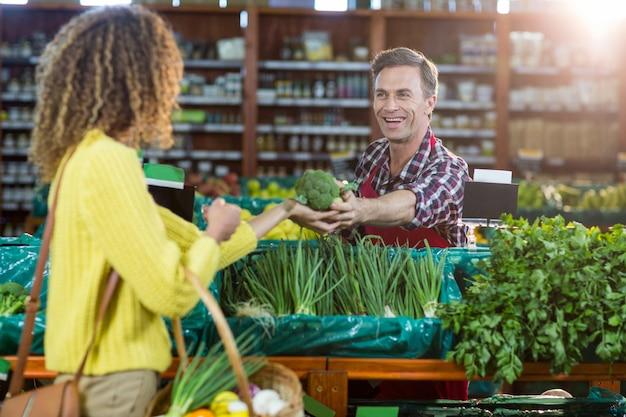 Personale maschile sorridente che assiste una donna con la spesa di drogheria