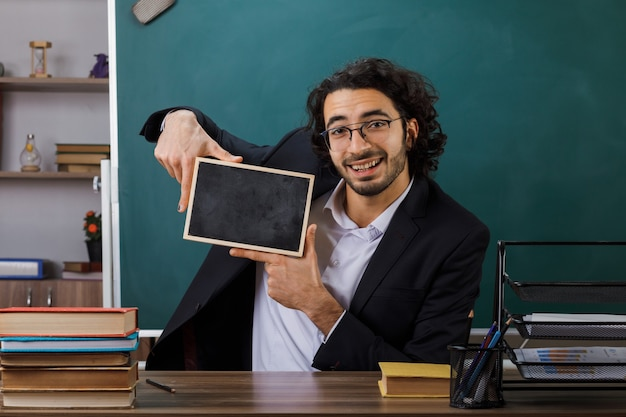 Insegnante maschio sorridente con gli occhiali che tiene mini lavagna seduta a tavola con gli strumenti della scuola in aula