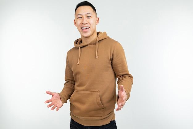 Uomo sorridente in maglia con cappuccio marrone con a braccia aperte su un bianco