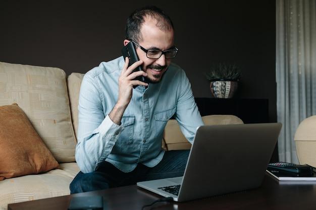 Uomo sorridente che chiama da casa mentre sta leggendo le notizie sul computer portatile. telelavoro e concetto di lavoro a distanza