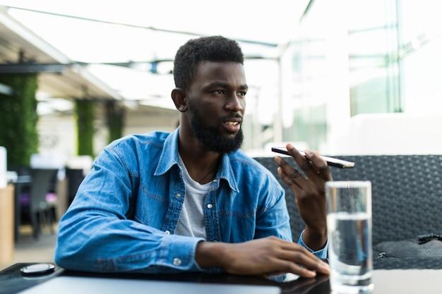 Uomo sorridente in una conversazione sul telefono all'aperto.