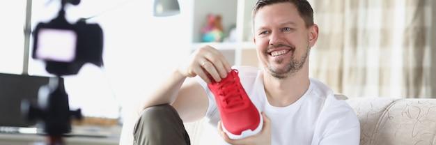L'uomo sorridente mostra la scarpa da tennis sulla videocamera