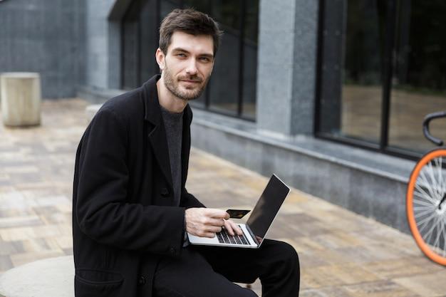 Uomo sorridente vestito con cappotto seduto in strada, utilizzando il computer portatile