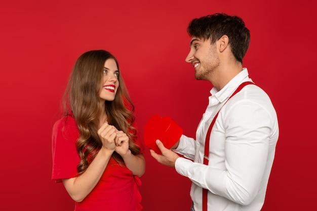 Uomo sorridente gifting cuore alla ragazza felice isolata