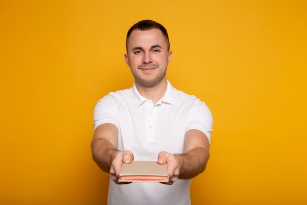 Uomo sorridente che dà libro sul giallo