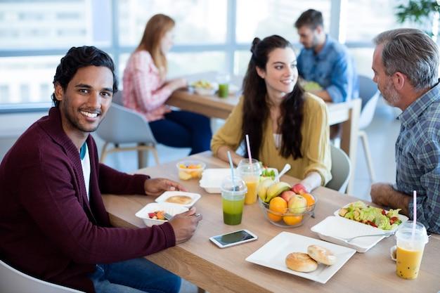 Uomo sorridente che mangia con i suoi colleghi in ufficio