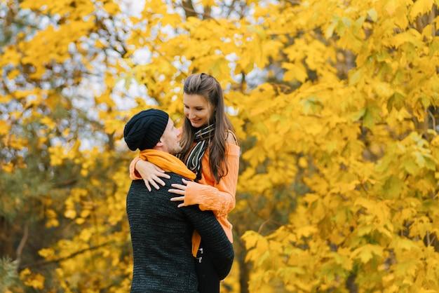 Un uomo sorridente tiene una donna tra le braccia
