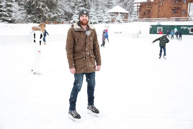 Uomo sorridente che pattina sul ghiaccio all'aperto con la neve