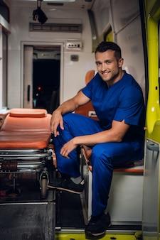 Uomo sorridente in un'uniforme medica che si siede nella parte posteriore di un'auto dell'ambulanza