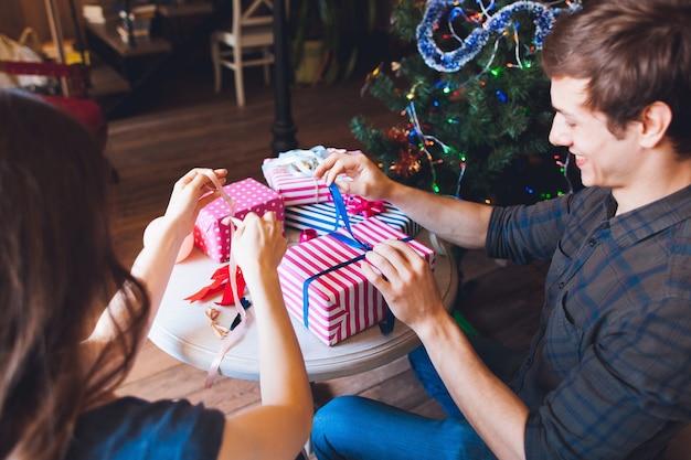 Uomo sorridente che confeziona regali con la moglie.