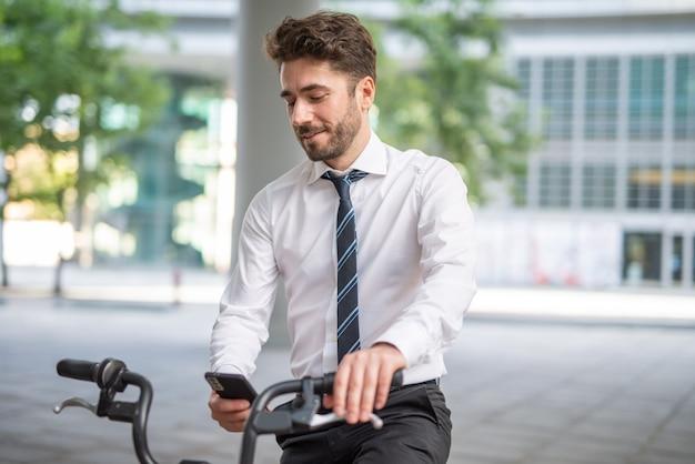 Uomo sorridente che parcheggia la sua bicicletta davanti all'ufficio