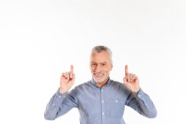 Uomo sorridente che indica in su con le dita e isolato