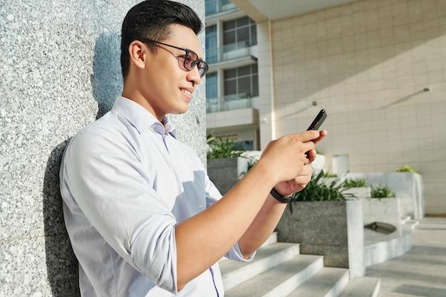 Uomo sorridente che legge il messaggio di testo