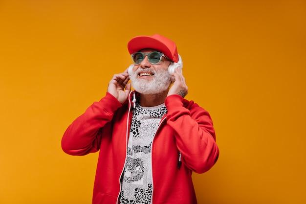 Uomo sorridente in abito rosso che sorride e ascolta musica in cuffia