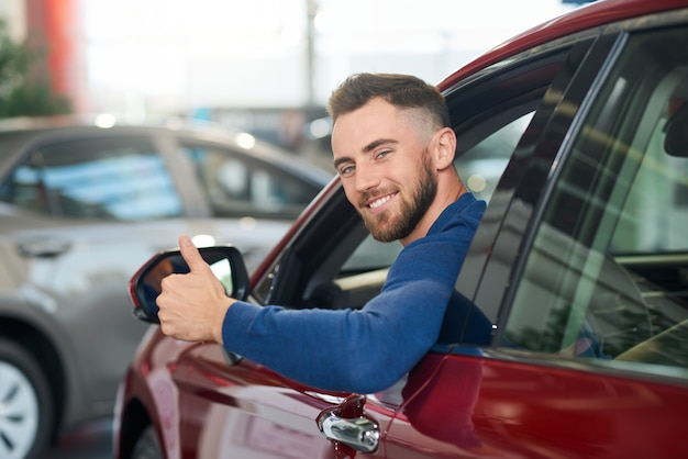 Uomo sorridente che mostra pollice in su in automobile.