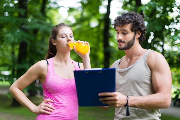 Uomo sorridente che mostra una tabella di addestramento ad una donna